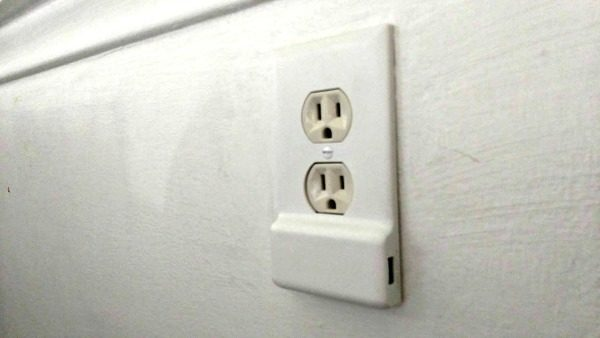 The Snap Power Charger Outlet Cover snugs the charger cord close to the wall.